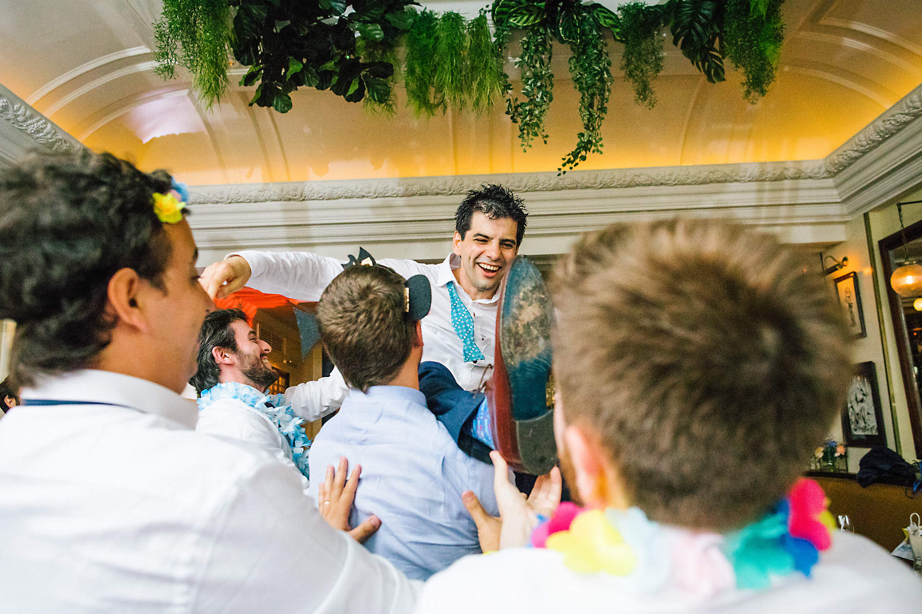 groom thrown in air at wedding